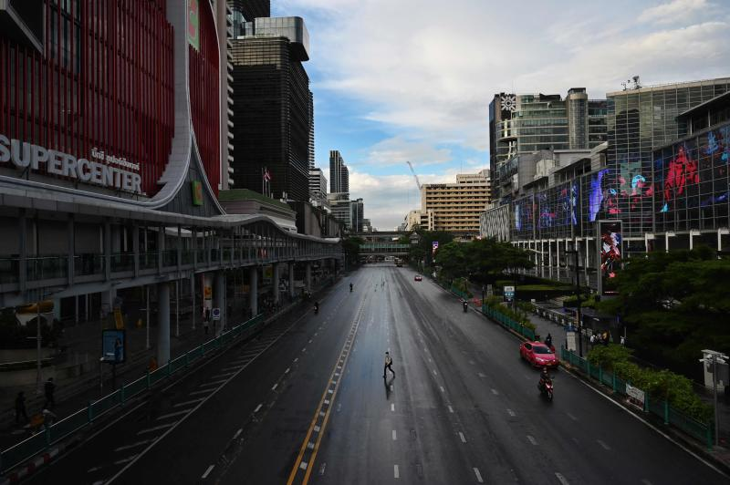 A man crosses the road on Ratchaprasong intersection in Bangkok on Monday, the first day of stricter lockdown restrictions to try to contain the spread of the Covid-19 coronavirus. (AFP photo)