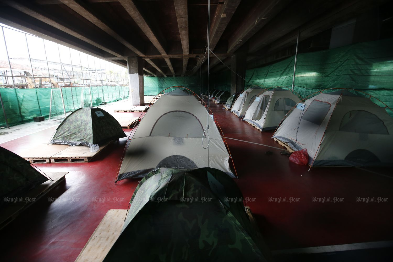 Tents are seen under the Expressway in Klong Toey district in Bangkok on Monday. Covid-19 infected people in communities stay in them while waiting to be sent to hospitals. (Photo by Wichan Charoenkiatpakul)