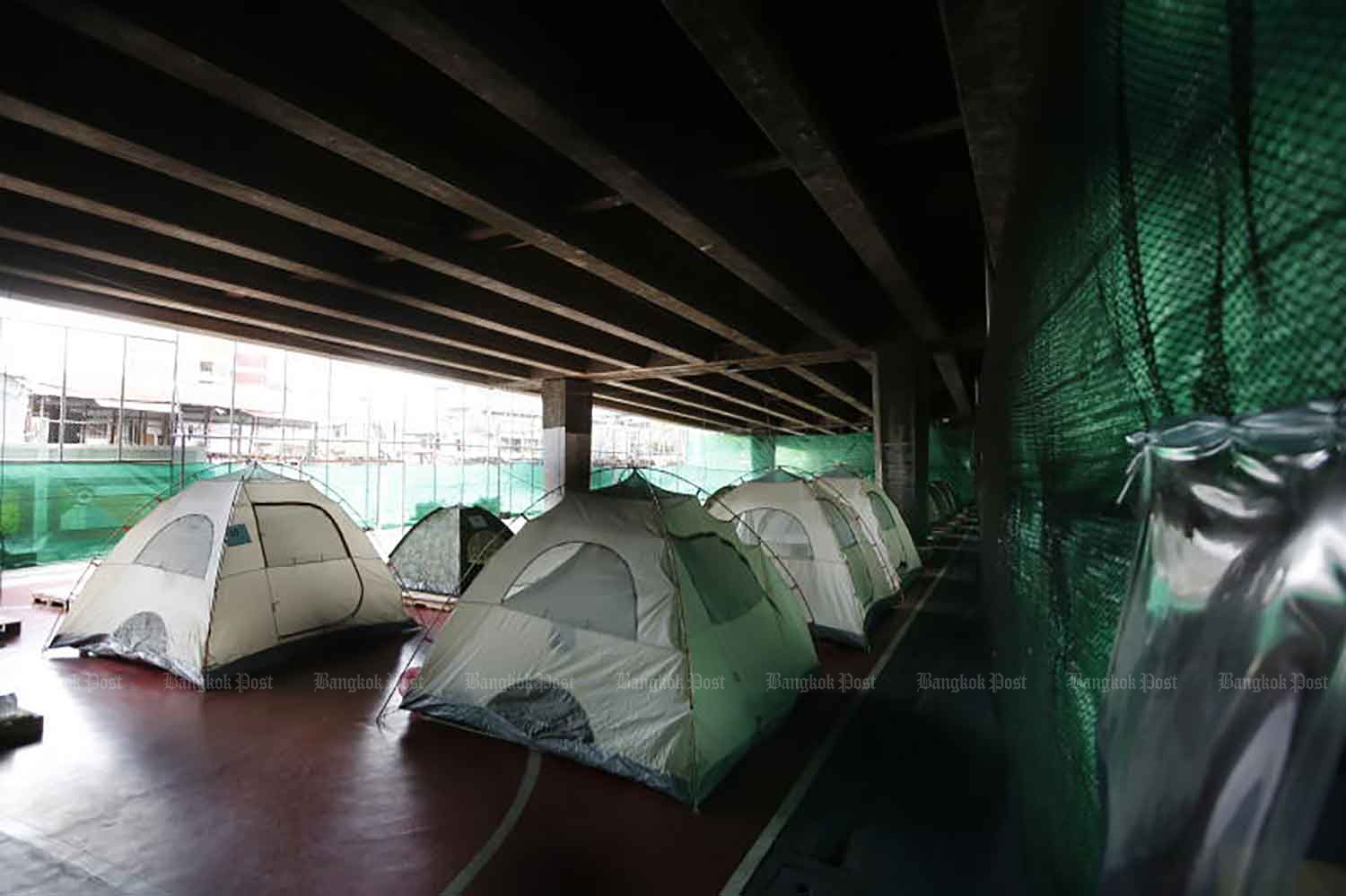 Tents were set up on a sports field under the elevated expressway in Klong Toey district, Bangkok, on Monday to isolate asymptomatic Covid-19 cases in a bid to control the virus. (Photo: Wichan Charoenkiatpakul)