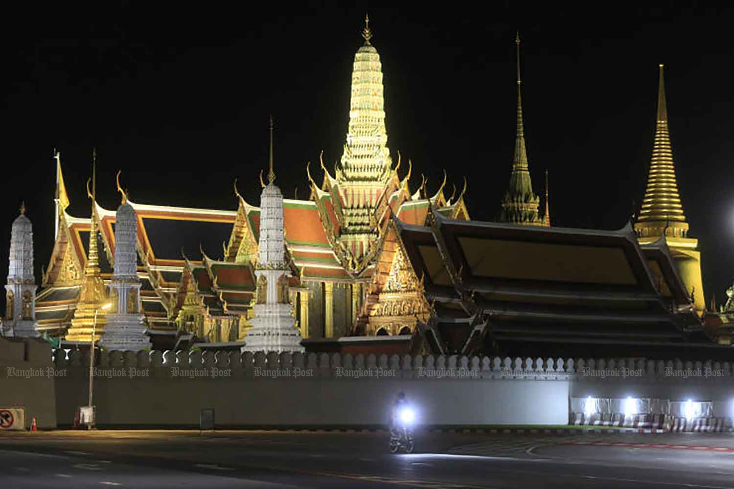 The road outside the Grand Palace is almost empty of traffic in the late evening, hours before the lauch of the 9pm-4am curfew on Monday night as part of wider measures to limint the transmission of Covid-19 in the 10 hardest-hit provinces, including Bangkok. (Photo: Pornprom Satrabhaya)