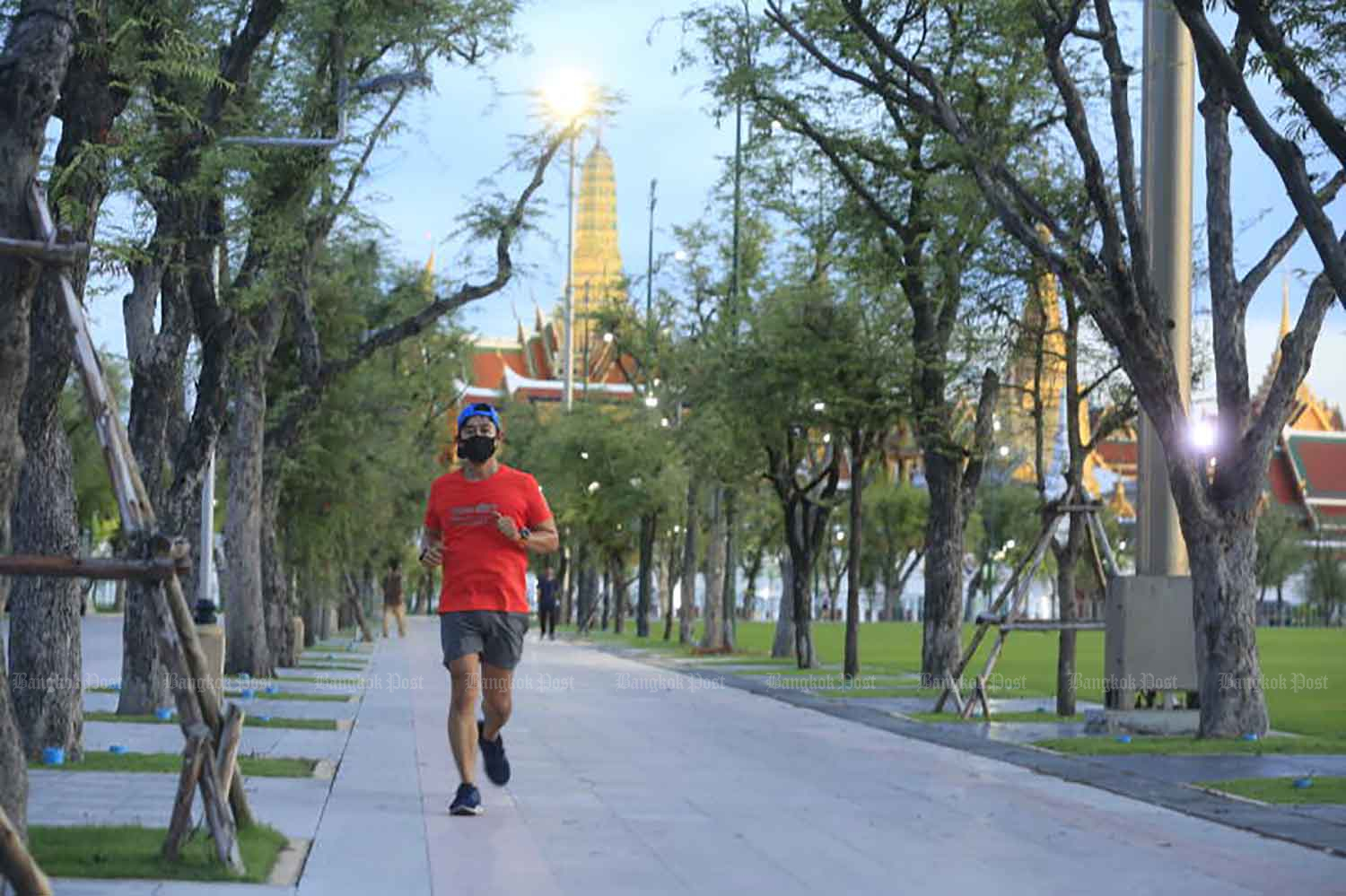 A man jogs near the Grand Palace in Bangkok on Monday evening, shortly before the 9pm-4am curfew came into force. (Photo: Pornprom Satrabhaya)