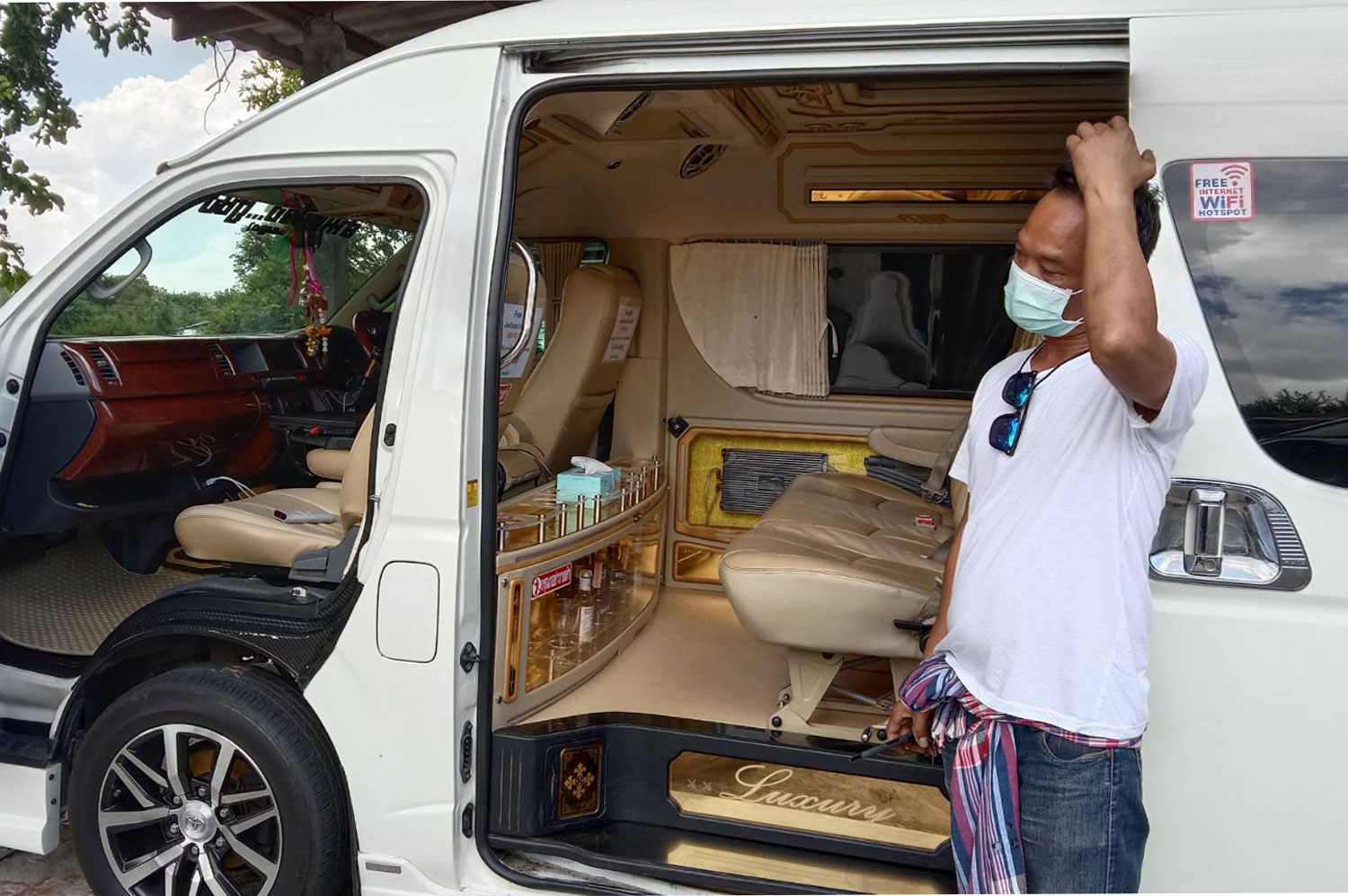 Punnawit Jaenlue, 41, a tour van operator in Nakhon Ratchasima, cleans his vehicle - but he has no customers, with interprovincial travel discouraged by the government's Covid-19 control measures. (Photo: Prasit Tangprasert)