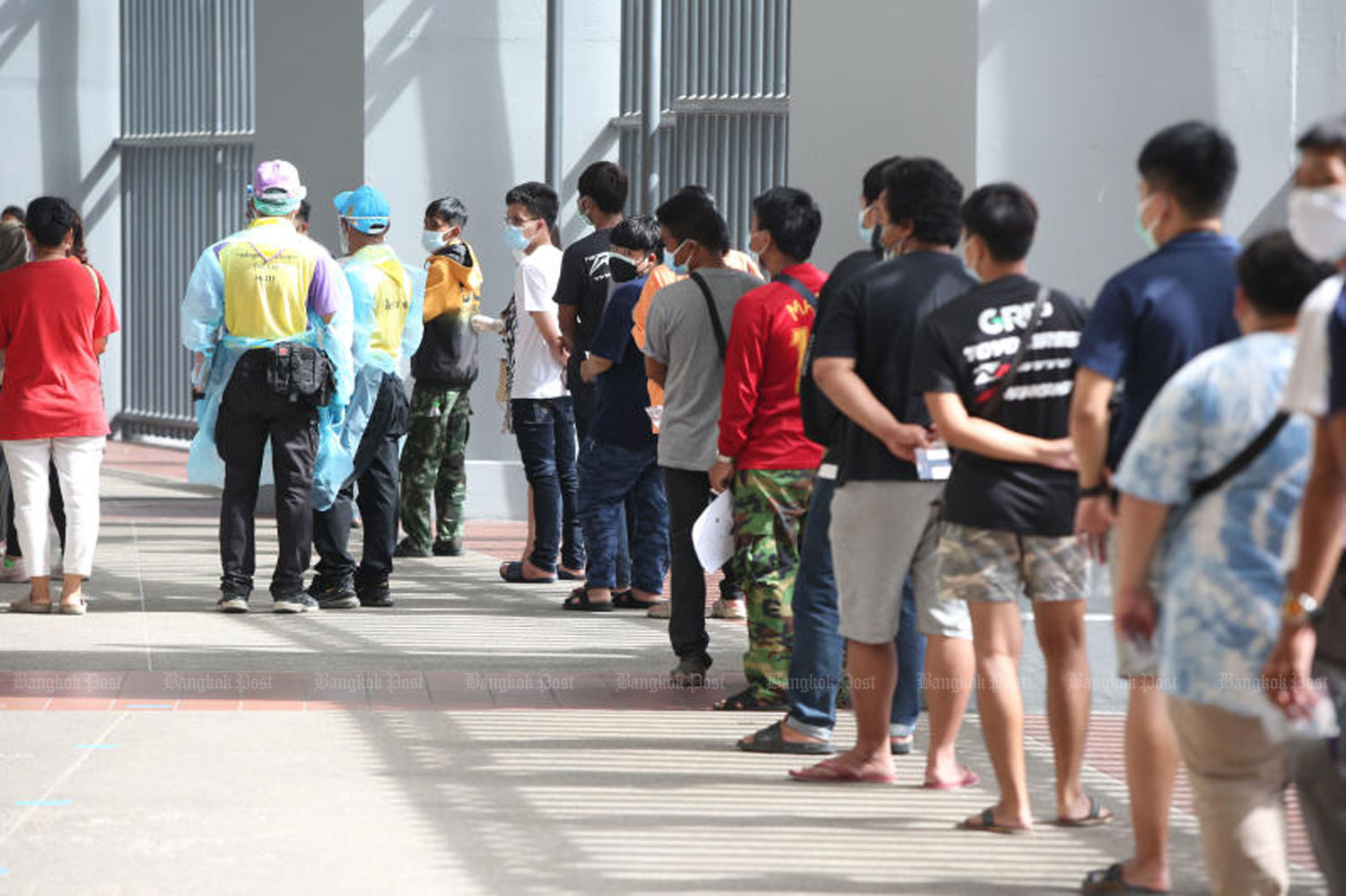People queue up for rapid Covid-19 antigen testing at Bangkok's Rajamangala National Stadium on Tuesday. About 1,500 people sought to get tested. (Photo: Varuth Hirunyatheb)