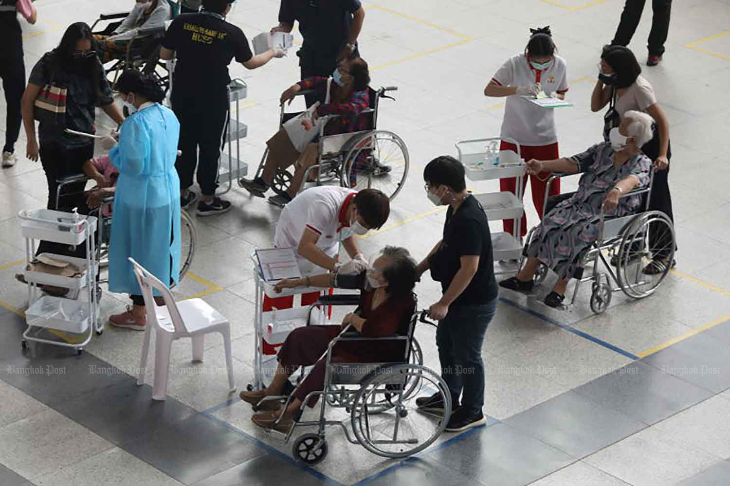 Elderly people are at the Bang Sue Grand Station for Covid-19 vaccination on Tuesday. (Photo: Arnun Chonmahatrakul)