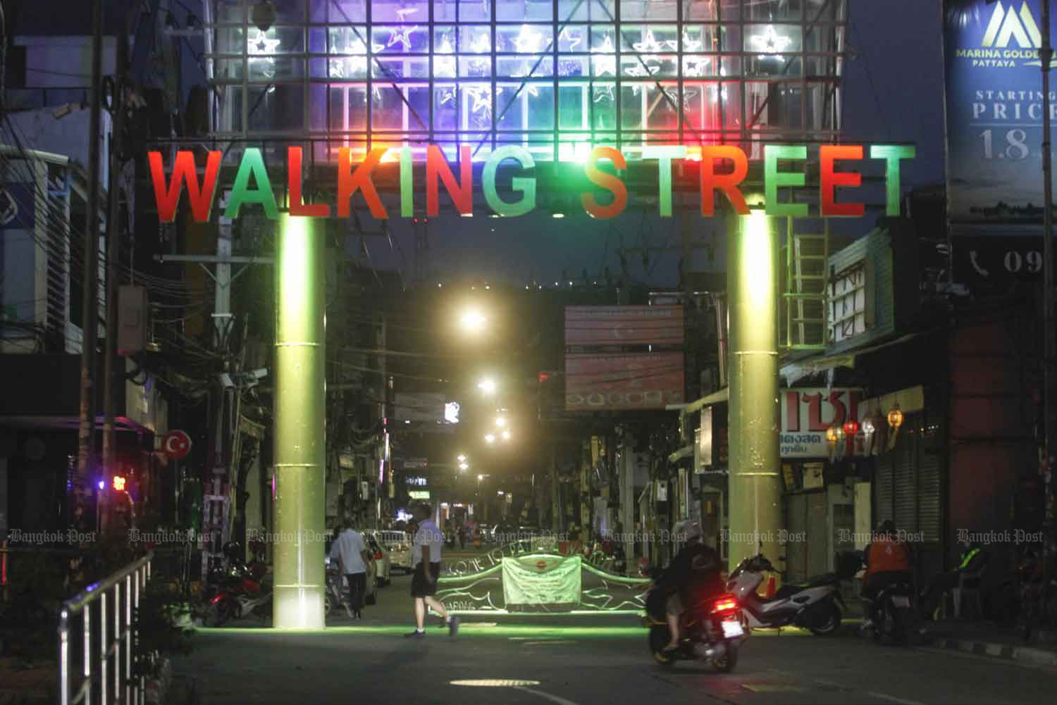 A sign lights up the entrance to Walking Street in Pattaya where business has ground to a halt since the onset of the Covid-19 pandemic. Nutthawat Wicheanbut
