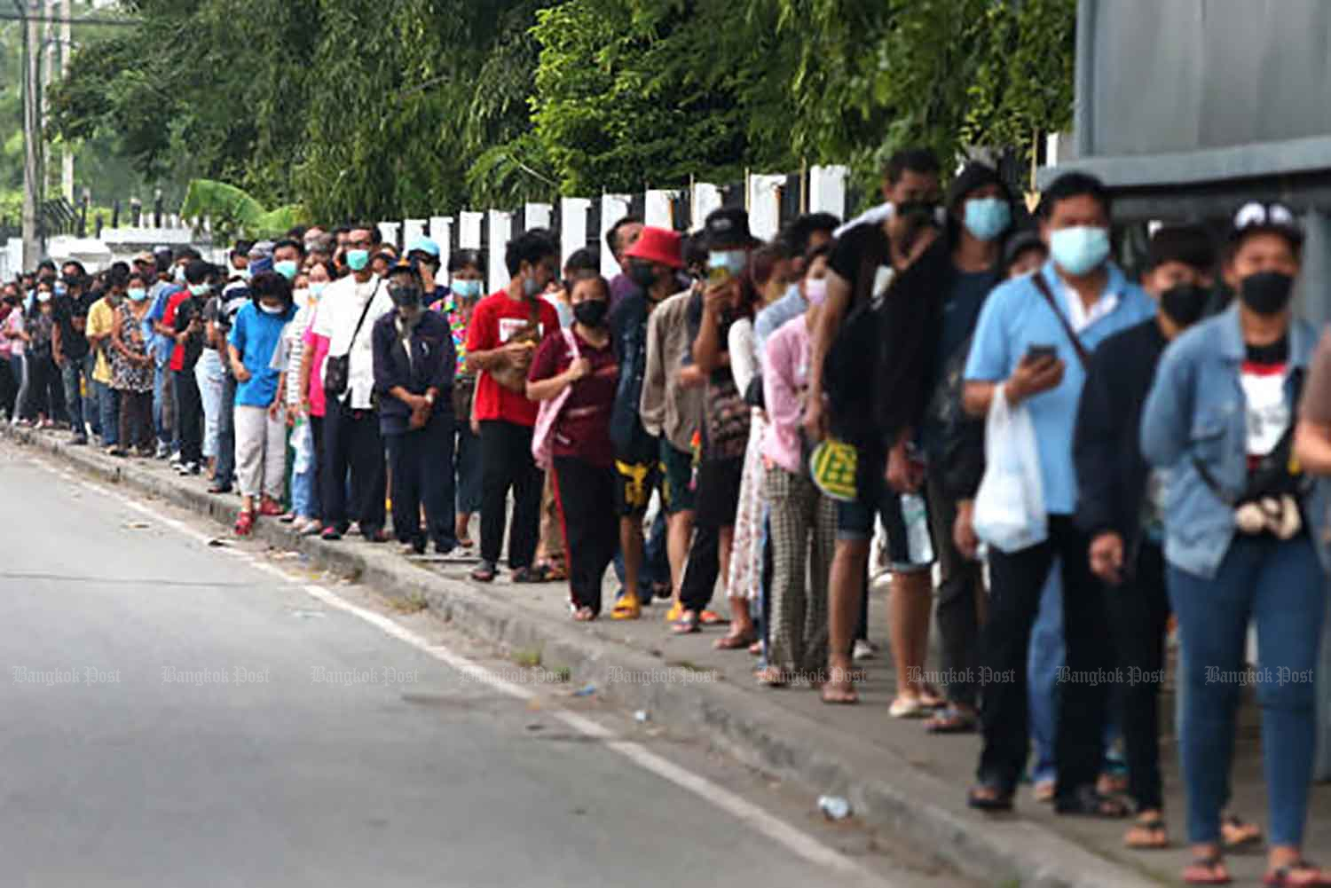 A long queue gathers outside Thupatemi Stadium, one of the centres opened for Covid-19 Rapid Antigen tests, in Don Muang district of Bangkok on Wednesday. More test locations have opened to handle increasing demand. (Photo: Varuth Hirunyatheb)
