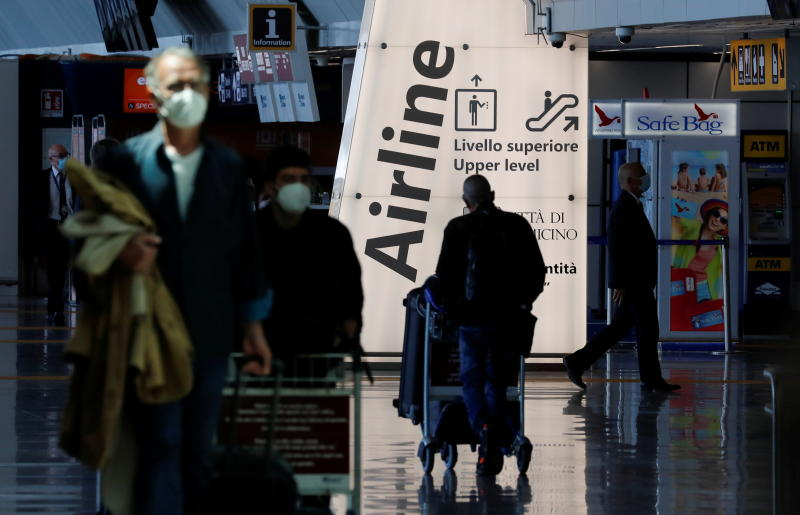 Travellers walk with their luggage at Fiumicino Airport in Rome on May 17, 2021 after Italy lifted quarantine restrictions to revive the tourism industry. (Reuters photo)