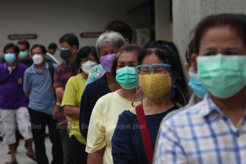 People flock to Siriraj Hospital on Friday for a free Sinopharm vaccine dose, donated by the Chulabhorn Royal Academy. The deteriorating Covid-19 situation was cited by Syn Mun Kong Insurance in terminating its clients' coronavirus insurance policies. (Photo: Apichart Jinakul)