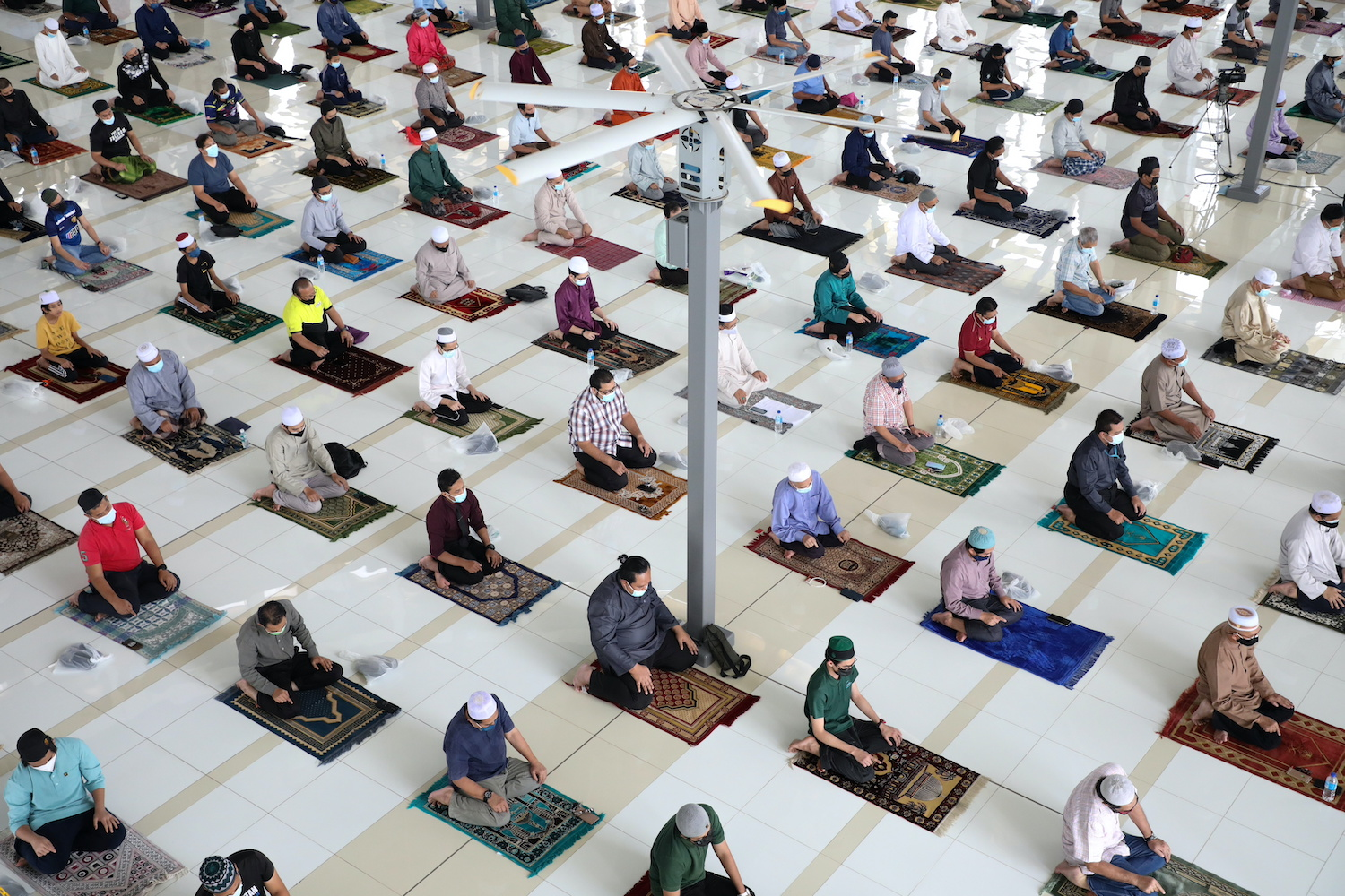 Worshippers follow social distancing measures while praying inside a mosque in Putrajaya, Malaysia on Friday. (Reuters Photo)