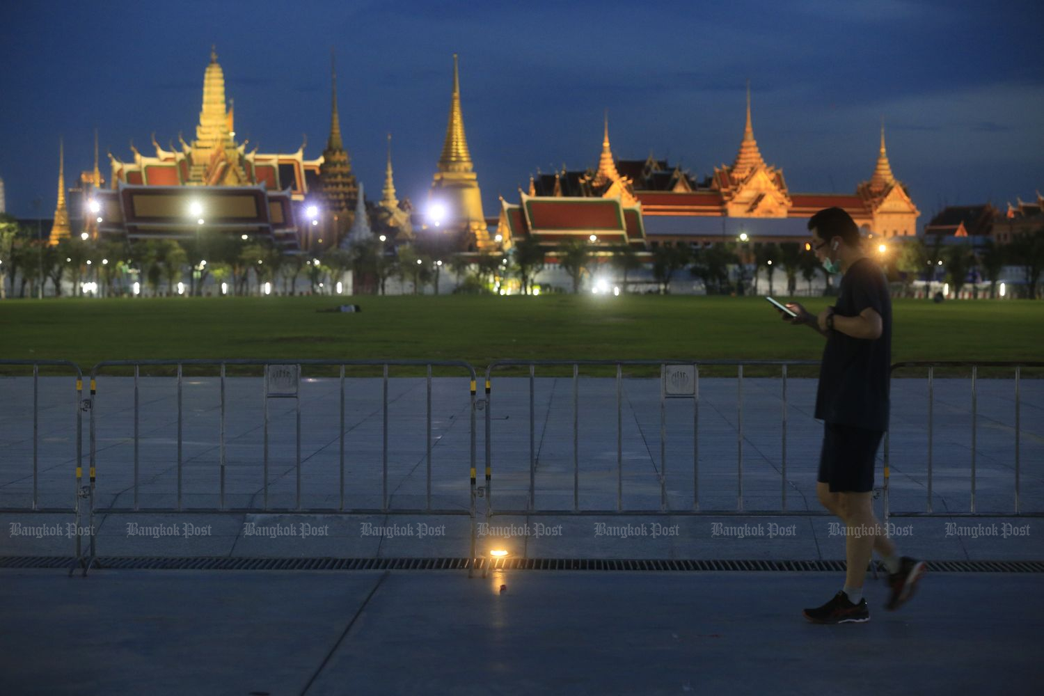 The road outside the Grand Palace in Bangkok is almost empty of traffic on Monday evening, hours before the launch of the 9pm-4am curfew. (Photo by Pornprom Satrabhaya)