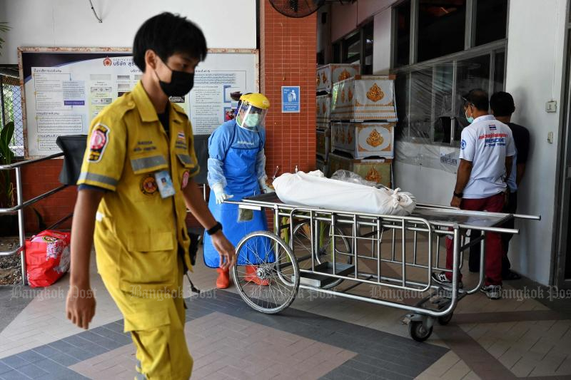 A hospital worker transports a body into the morgue of Thammasat University Hospital, in Pathum Thani province just north of Bangkok, on Saturday. (AFP photo)