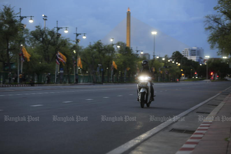 A motorcyclist rides on deserted Ratchadamnoen Avenue near Sanam Luang shortly before the curfew begins on July 12, 2021. Lockdown measures have been extended to Aug 2. (Photo: Pornprom Satrabhaya)