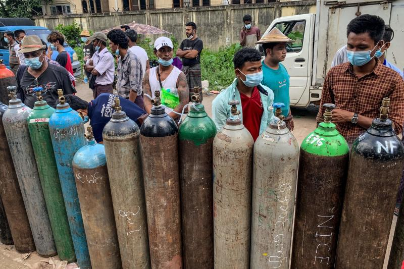This picture taken on July 14, 2021 shows people waiting to fill up empty oxygen canisters outside a factory in Yangon, amid a surge in the number of Covid-19 coronavirus cases. (AFP)