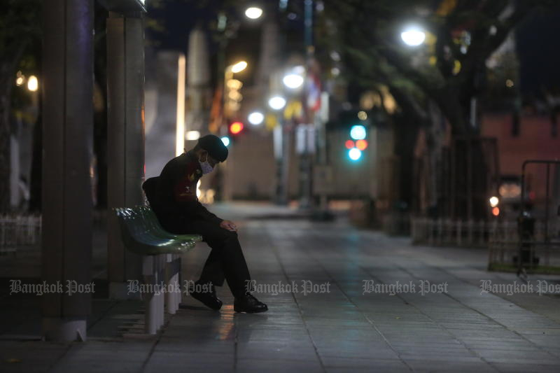 A man waits for a bus at Sanam Luang before the curfew starts at 9pm on July 12, 2012. (Photo: Pornprom Satrabhaya)