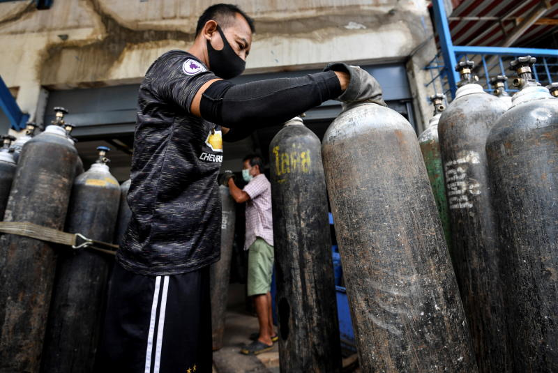 An employee wearing a protective mask delivers medical-use oxygen cylinders from a store to a hospital, to help coronavirus disease patients, as demand for oxygen continues to grow amid the Covid-19 pandemic, in Bangkok, on Saturday. (Reuters photo)