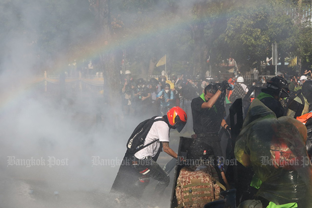 Anti-government protesters clash with police on Ratchadamnoen Avenue blocking their march to Government House on Sunday. (Photo: Arnun Chonmahatrakool)