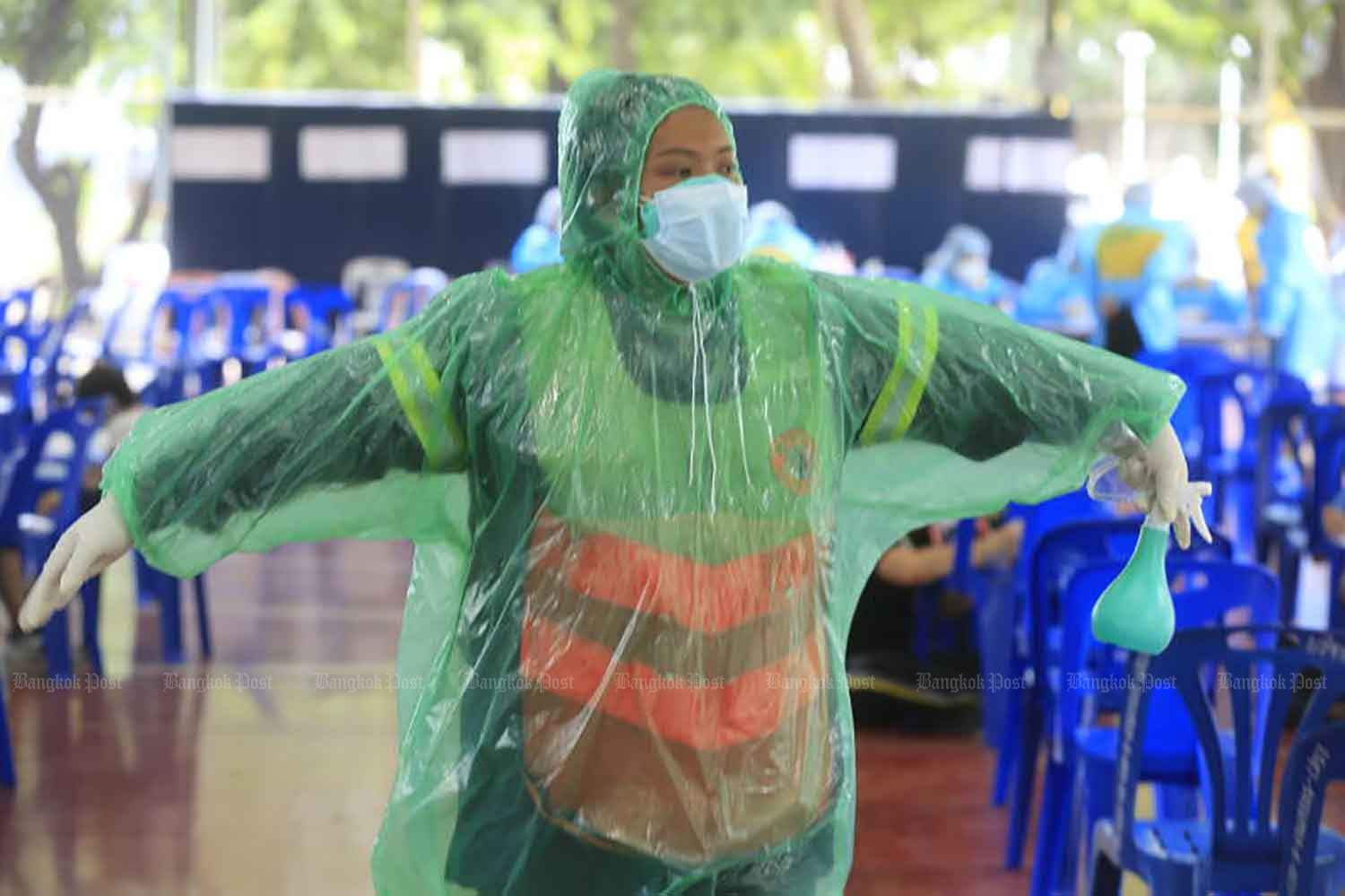A City Hall worker shows off her improvised protective gear made from a plastic raincoat, as officials from Chatuchak district office assist people arriving for  Covid-19 testing at the sports ground at Chadrakasem Rajabhat University in the capital on Monday. (Photo: Pornprom Satrabhaya)