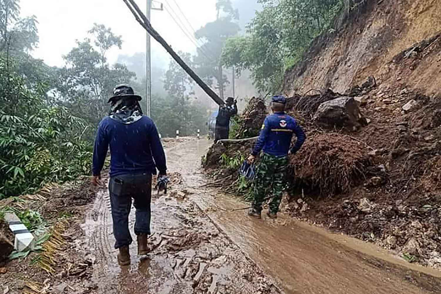Soldiers from the 33rd Mobile Development Unit clear a landslip from Highway 105 near kilometre marker 81 on Monday morning in Tak's Tha Song Yang district. It was blocked overnight during a rainstorm. (Photo: Assawin Pinitwong)