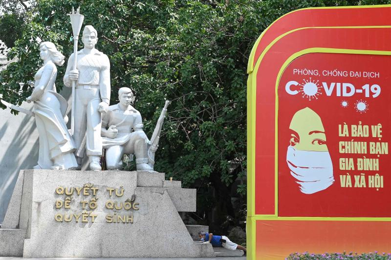 A man (centre) exercises besides a hoarding urging the public to prevent the spread of the Covid-19 coronavirus in Hanoi on Monday. (AFP photo)