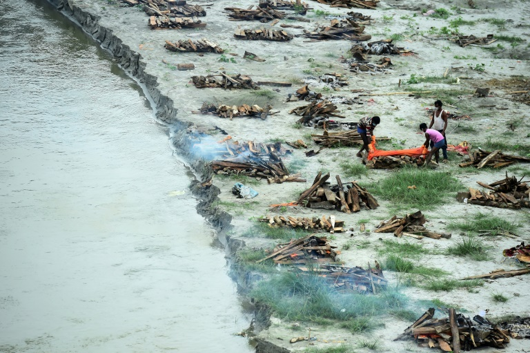 Municipal corporation workers prepare to cremate a body buried in a shallow grave on the bank of the Ganges river during the Covid-19 pandemic in India.