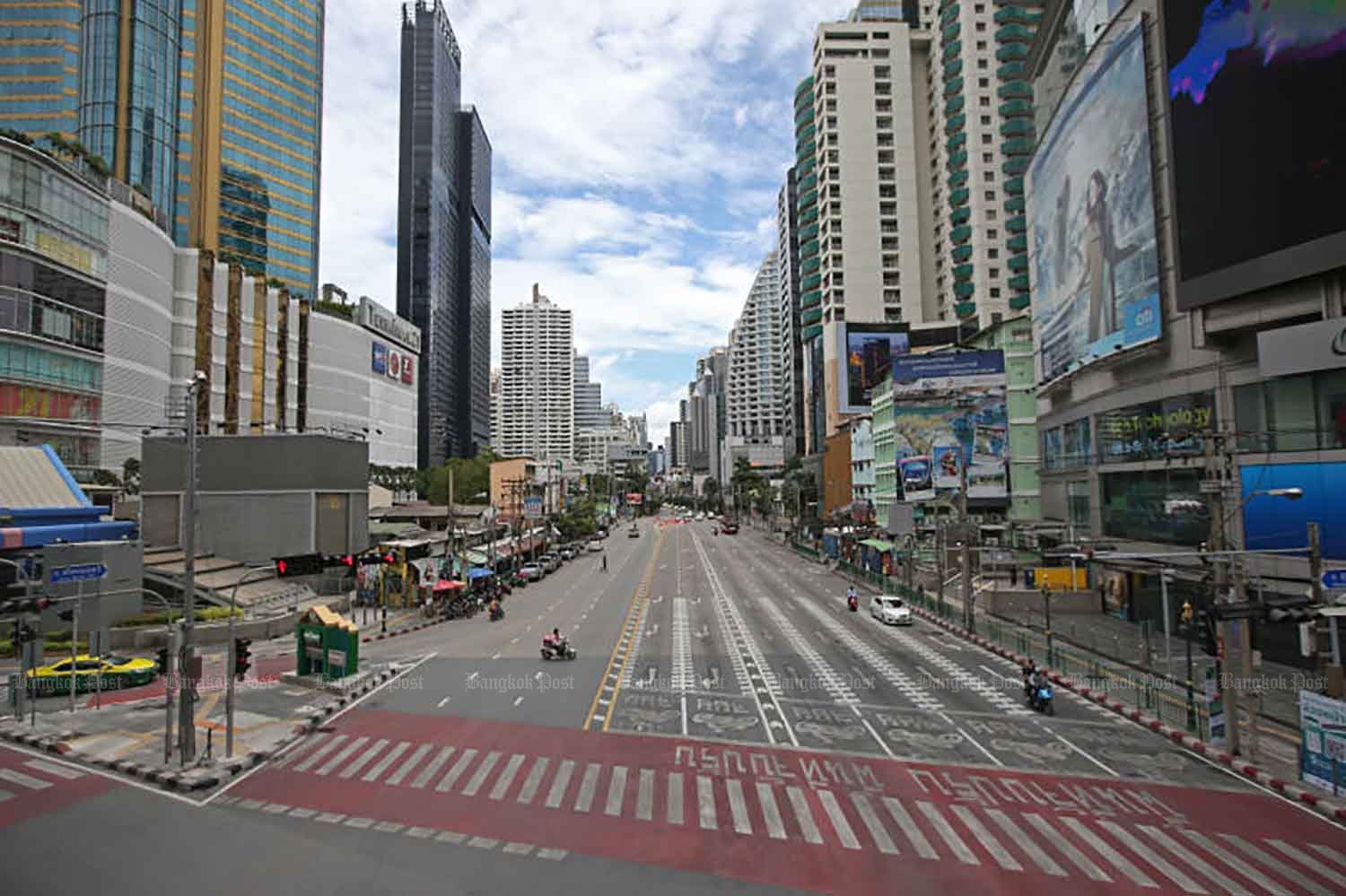 Normally bustling Asoke intersection is seen with very light traffic after the full lockdown took effect on Tuesday in 13 provinces hardest-hit by the pandemic, including Bangkok. Stepped-up curbs are intended to lower surging daily infections which have exceeded 10,000 in the past several days.  (Photo: Varuth Hirunyatheb)
