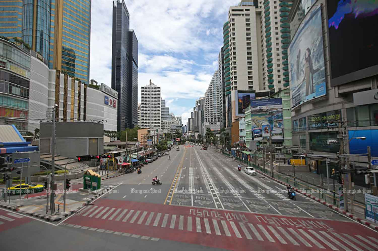 Normally bustling Asoke intersection after full lockdown took effect on Tuesday in 13 provinces hardest hit by the pandemic, including Bangkok. (Photo: Varuth Hirunyatheb)