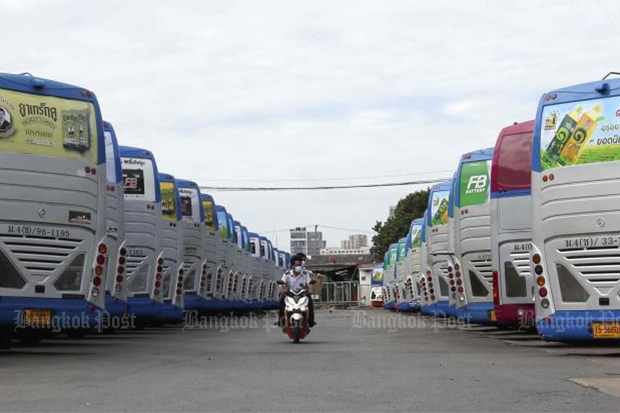 A worker at Transport Co, a state enterprise under the Transport Ministry, rides a motorcycle past a fleet of idled interprovincial buses at Mor Chit terminal after service suspension started on Wednesday. (Photo: Pattarapong Chatpattarasill)