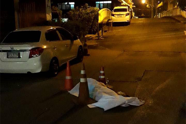 A dead man lies in the middle of the road, covered by a sheet, hours after he died, on Soi Ban Phanthom, off Phra Sumeru Road, in Phra Nakhon district of Bangkok on Tuesday night. (Photo from Phuri Phatara Facebook account)