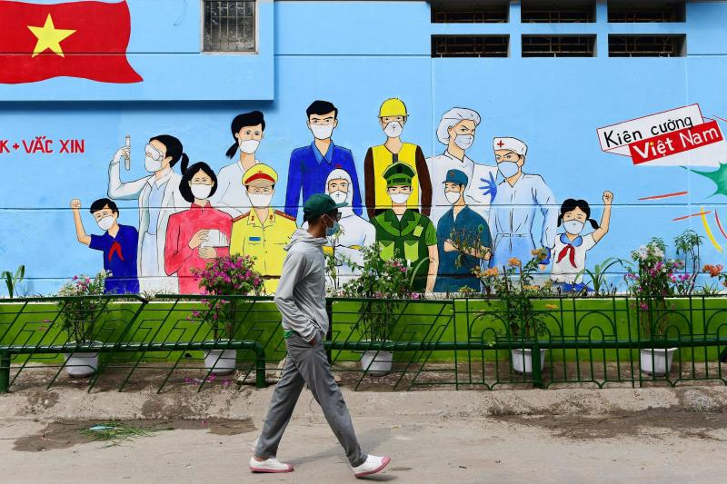 A man walks past a mural depicting Covid-19 coronavirus frontline workers outside a building in Hanoi on Monday. (AFP photo)