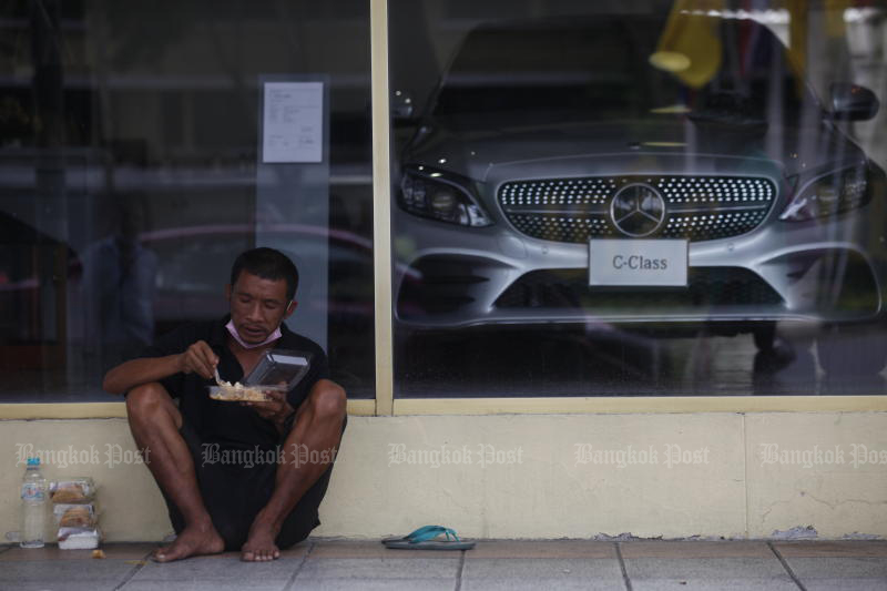 A man eats food on the pavement along Ratchadamneon Avenue on Wednesday. The Covid-19 pandemic affects people and the media industry. (Photo: Nutthawat Wicheanbut)