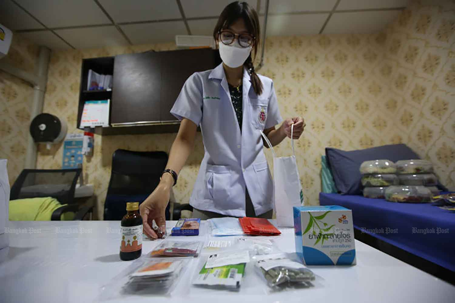 A doctor prepares medication to be delivered to Covid-19 patients under home isolation in Kannayao district of Bangkok on Wednesday. The programme allows those with mild symptoms to stay at home, in order to help ease workloads at hospitals. (Photo: Varuth Hirunyatheb)