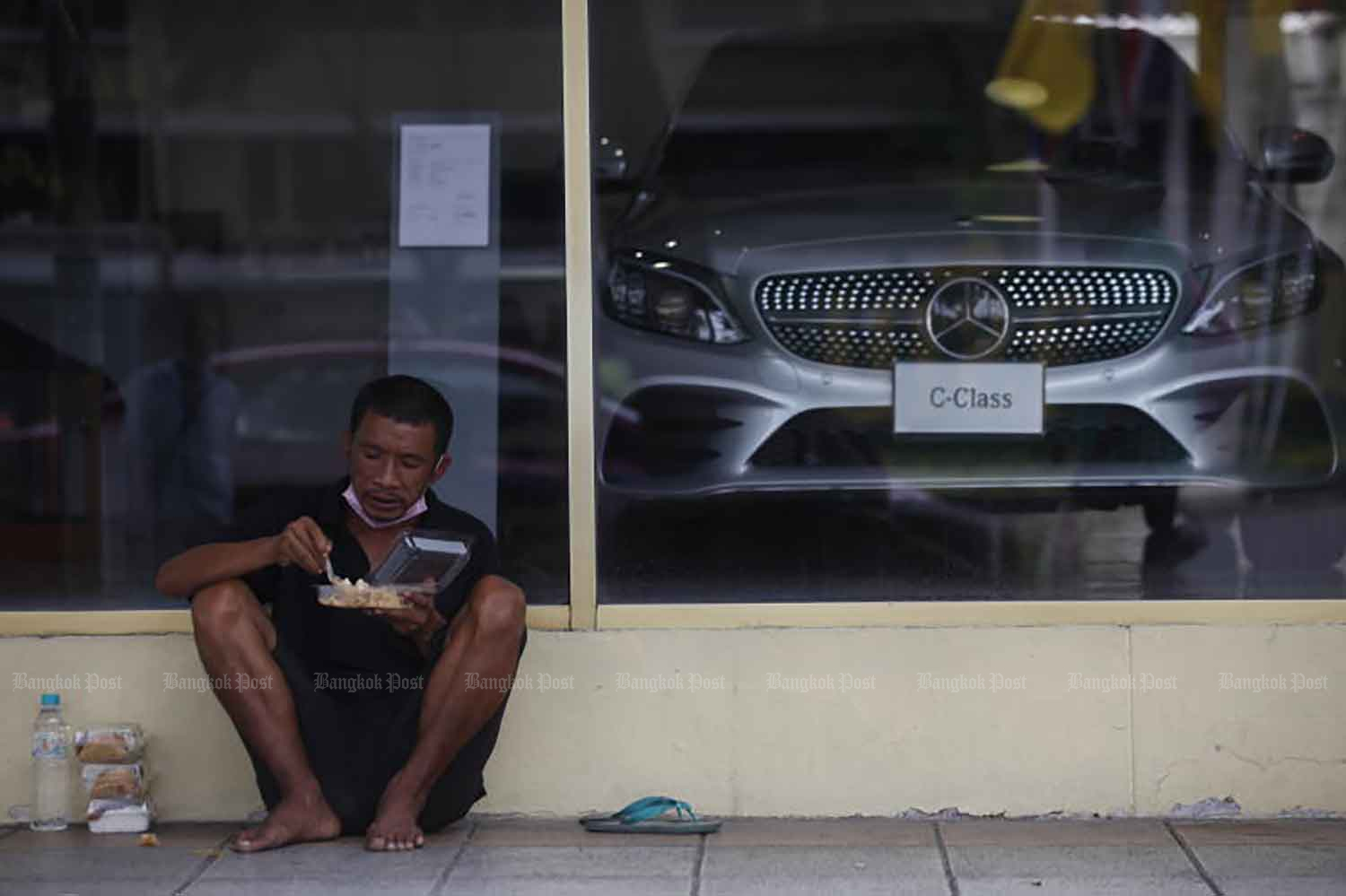 A man downs a meal outside a luxury car showroom near the Democracy Monument in Bangkok on Wednesday. The Covid-19 crisis has prompted many people to give food to homeless people on the streets. (Photo: Nutthawat Wicheanbut)