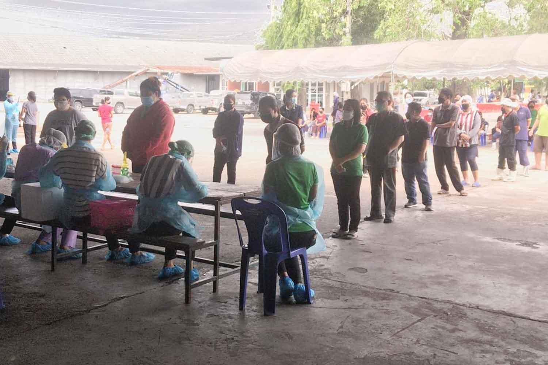 Workers queue up for Covid-19 tests at Vita Food Factory (1989) in Tha Maka district, Kanchanaburi, on Thursday. (Photo: Piyarat Chongcharoen)