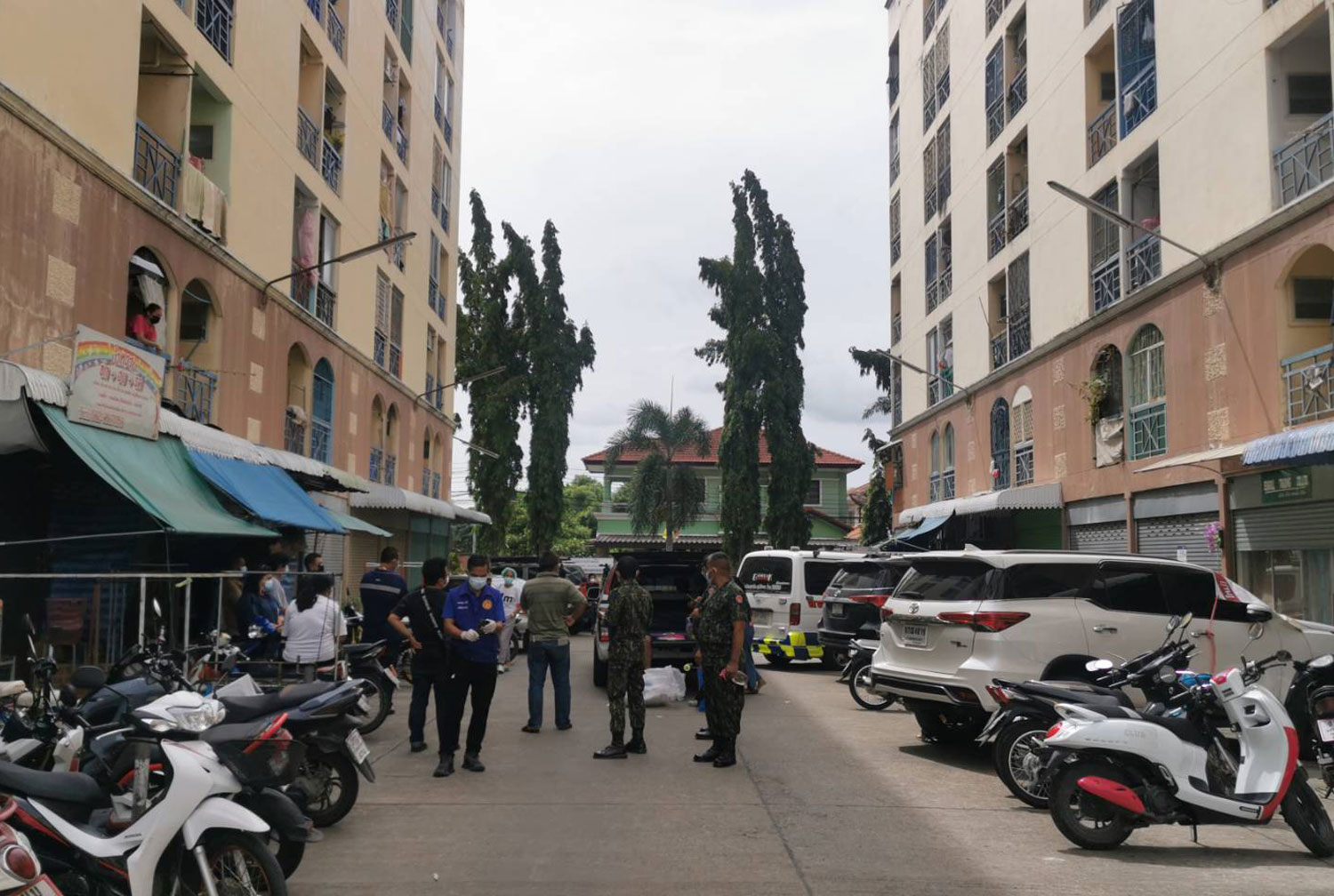 Officials gather at the condo building where an elderly Covid-infected security guard waiting for a hospital bed hanged himself on Thursday morning, in Bang Bua Thong district of Nonthaburi province. (Photo supplied via Wassayos Ngamkham)