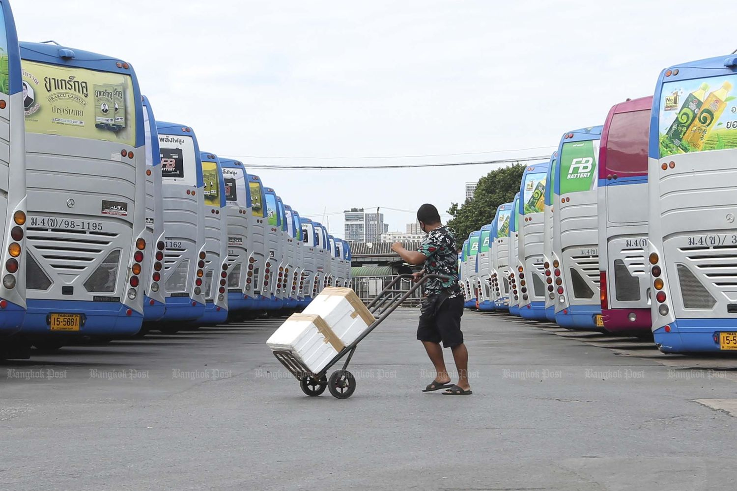 A man moves boxes at the Mor Chit bus terminal in Bangkok on Wednesday, the first day interprovincial bus services were suspended to contain the Covid-19 outbreak. The temporary suspension ends on Aug 2. (Photo by Pattarapong Chatpattarasill)