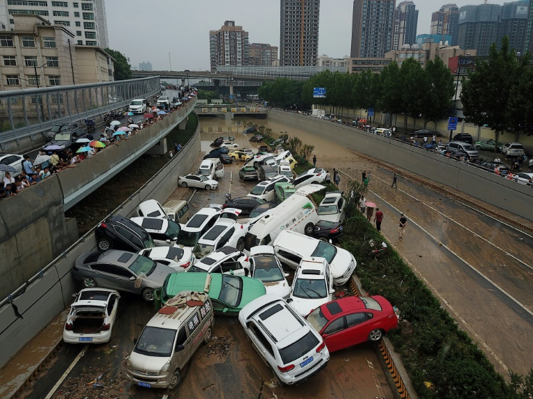 Cars were left strewn over roads after heavy rain hit the city of Zhengzhou.