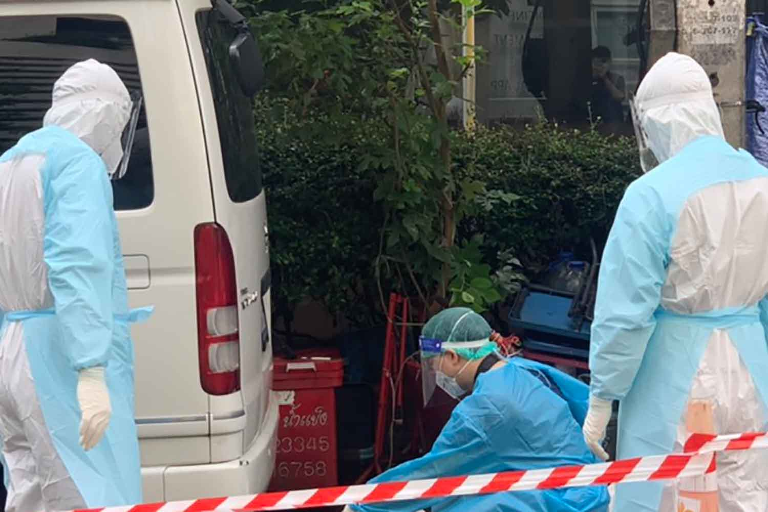 Medical workers in protective suits examine the body of a man found dead on Soi Sukhumvit 20 in Watthana district, Bangkok, on Thursday morning. (Photo supplied)
