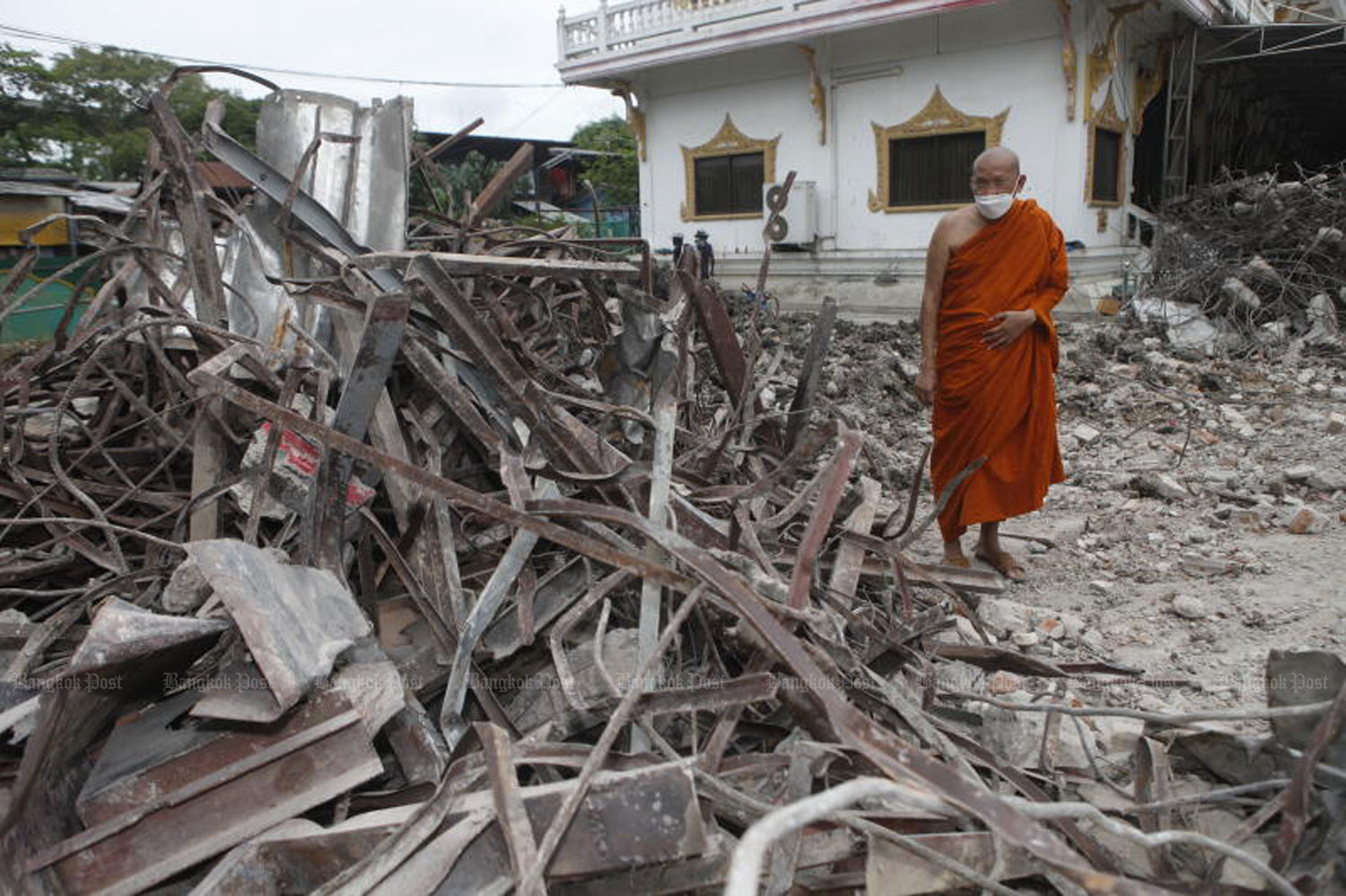 Phra Khru Patra Waranusit, assistant abbot of Wat Bang Nam Chon in Thon Buri district, Bangkok, inspects the temple's demolished crematorium on Friday. The 25-year-old crematorium developed cracks early this month, worn out by heavy use during the Covid-19 epidemic. (Photo: Nutthawat Wicheanbut)