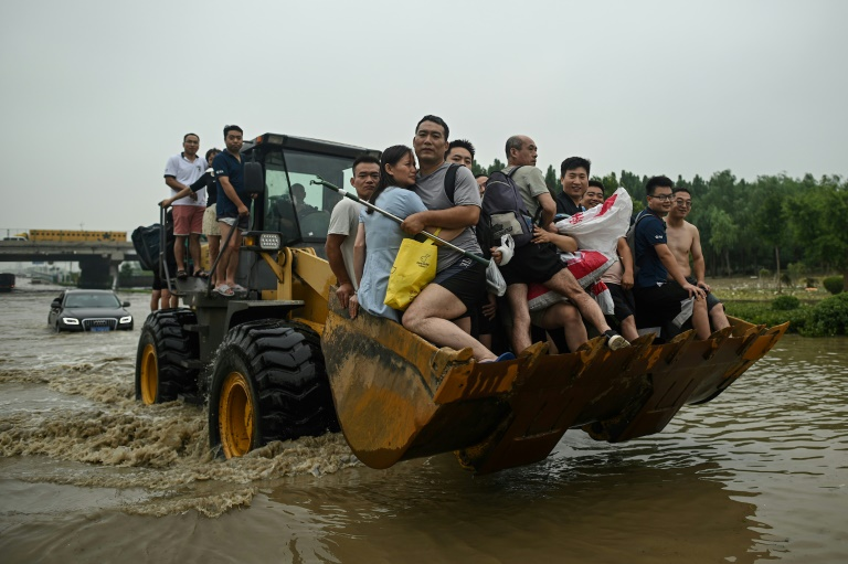People are carried across a flooded street in the worst-hit city of Zhengzhou, which received a year's worth of rain in just three days.