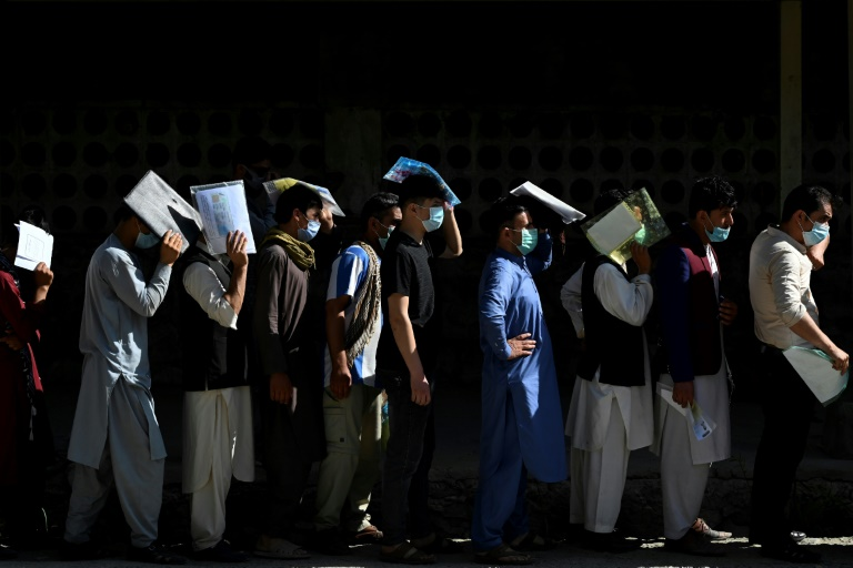 Afghan men line up to apply for a passport in Kabul, with a rush of applications ahead of the final withdrawal of foreign troops from the country.