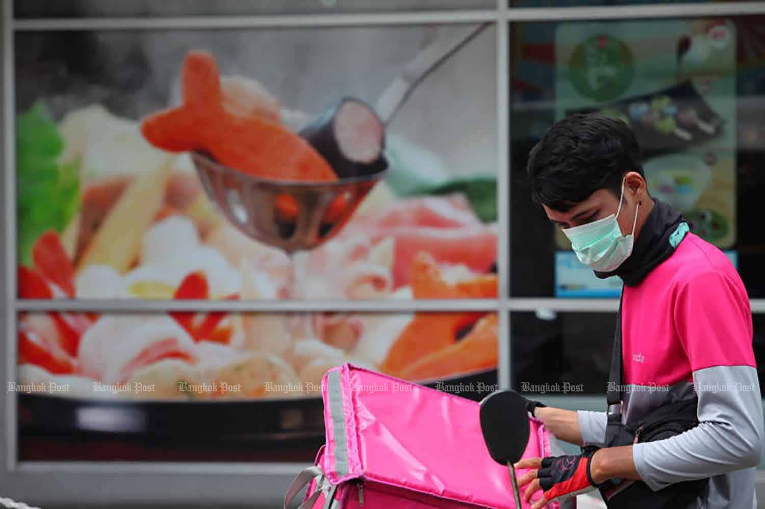 A delivery man stands by near an eatery at a shopping centre in Lat Phrao area of Bangkok last month. (Photo: Apichart Jinakul)