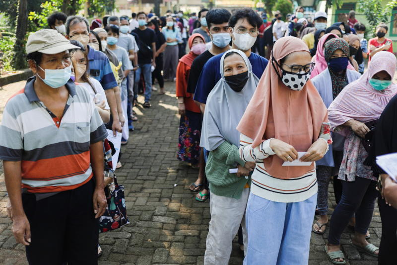 People wearing protective face masks queue to receive a dose of China's Sinovac Biotech vaccine for coronavirus disease (Covid-19) during a mass vaccination program at a school building in Jakarta, Indonesia on Monday. (Reuters photo)