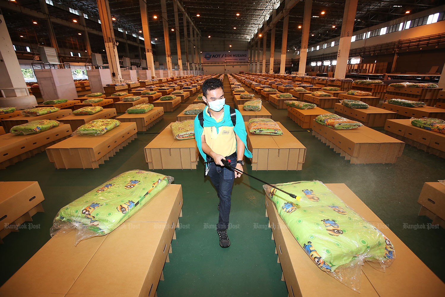 Covid cleaning: An official sprays disinfectant inside a warehouse which has been turned into a field hospital at Don Mueang airport. The field hospital, run by Mongkutwattana Hospital and capable of handling up to 2,000 patients, opened yesterday. (Photo: Pattarapong Chatpattarasill)