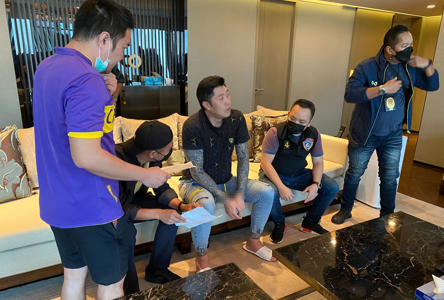 Plainclothes officers question Shuichi Ozawa, 42, for his alleged involvement in a 3-million-baht rubber glove fraud at a hotel in the Phloenchit area of Bangkok on Saturday evening. (Police photo)