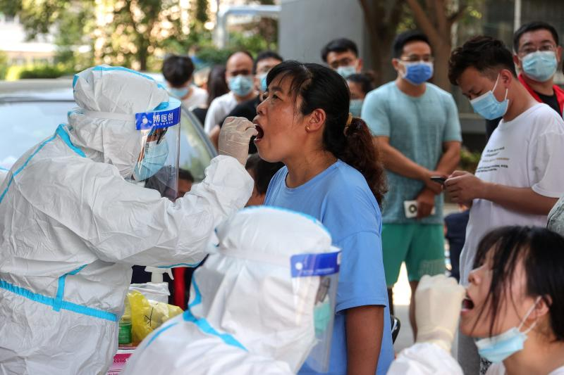 Chinese cities test millions as virus cases jump
