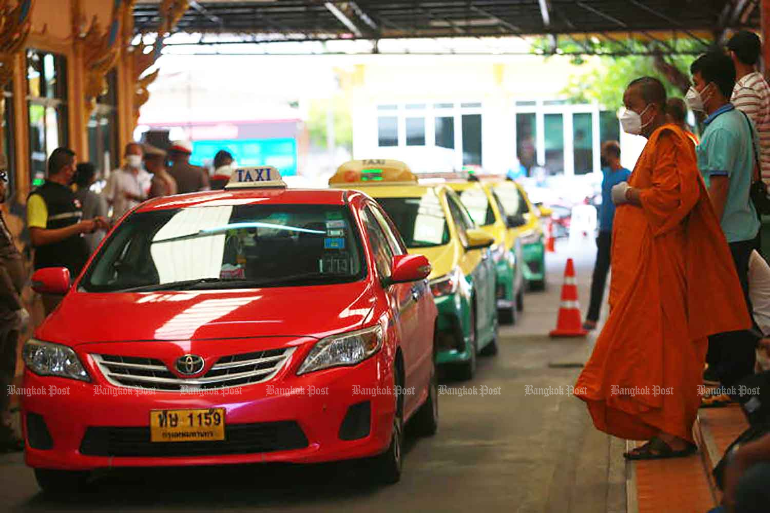 Taxi drivers queue up at Wat Bang Phli Klang in Samut Prakan province to receive donations on Thursday. The temple donated 500 baht in cash and 5kg of rice to each driver. (Photo: Somchai Poomlard)