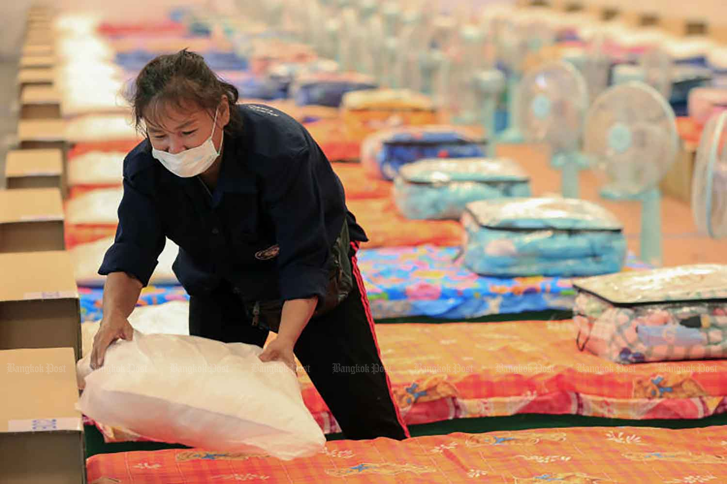 A worker prepares beds for a community isolation facility at the Tax Collection Training Institute building of the Revenue Department in Nonthaburi on Thursday. (Photo: Pornprom Satrabhaya)