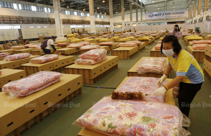 Volunteers prepare mattresses and blankets as an air cargo warehouse at Don Mueang airport is converted into a new field hospital before it opens on Thursday. (Photo: Apichit Jinakul)