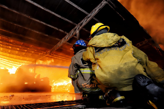 Firefighters try to douse a fire that engulfed a furniture factory of Aree Aphiluck Co in Muang district of Pathum Thani on Saturday. (Photo: Pongpat Wongyala)