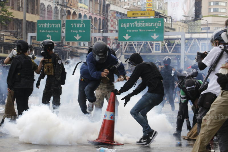Protesters react to tear gas during clashes with police near Victory Monument on Saturday. (Photo: Wichan Charoenkiatpaku)